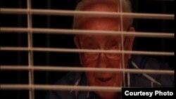 Lorenzo García Vega, escritor cubano, lee tras una persiana en su casa de Miami. Tomado de un video facilitado por Pedro Portal.