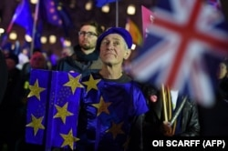 Anti-Brexit activists demonstrate with other protesters outside of the Houses of Parliament in central London on January 15, 2019. -