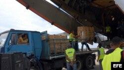 Trabajadores cubanos descargan paquetes de ayuda humanitaria.
