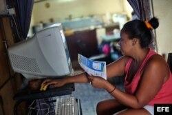 Una mujer intenta conectarse a internet en su casa en La Habana.