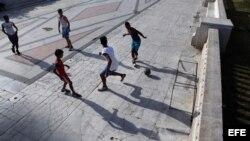 Jóvenes jugando fútbol en un parque en La Habana.
