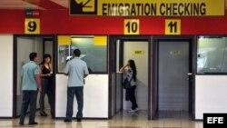 Dos mujeres chequean su pasaportes en las cabinas de emigración del aeropuerto Internacional José Martí en La Habana. Cuba.