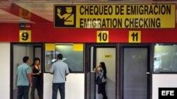 Dos mujeres chequean sus pasaportes en las cabinas de emigración del aeropuerto José Martí, en La Habana.