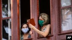 Dos residentes de La Habana graban con un teléfono a soldados de las Fuerzas Armadas que participan en labores de desinfección en la capital cubana, el 15 de abril del 2020.