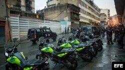 Efectivos de distintos cuerpos de seguridad custodian y toman evidencias de una explosión en la ciudad de Caracas.