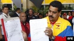 El presidente encargado de Venezuela, Nicolás Maduro (d), muestra su hoja de inscripción como candidato presidencial.