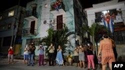 Vecinos de un barrio habanero aplauden el 30 de marzo a médicos y enfermeras que combaten el coronavirus en la capital de Cuba (Foto: Yamil Lage/AFP).