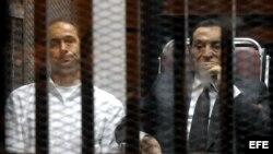 El expresidente egipcio Hosni Mubarak (d) y su hijo Gamal (i), fotografiados en la celda del tribunal mientras la corte dicta sentencia en El Cairo (Egipto) hoy, miércoles 21 de mayo de 2014.