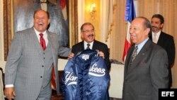 El presidente de República Dominicana, Danilo Medina (c), recibe una chaqueta del equipo de béisbol los Yankees de Nueva York de manos del fundador y presidente del Salón de la Fama de Béisbol Latino, Robert Weil (d), y del vicepresidente del equipo, Féli