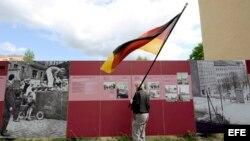 Un hombre con la bandera nacional observa el memorial del Muro de Berlín en Bernauer Strasse, Berlín Alemania. Archivo.