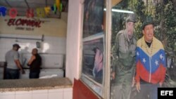 Dos hombres conversan en un establecimiento junto a un cartel de Hugo Chávez y Fidel Castro en La Habana (Cuba).