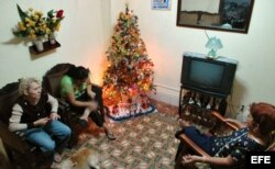 Tres mujeres conversan en una casa decorada con un árbol de Navidad.