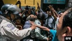 Un cordón policial separa al grupo de seguidores del opositor venezolano Leopoldo López, y otro grupo oficialista.