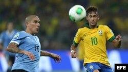 El delantero de la selección de Brasil, Neymar da Silva (d), lucha el balón con Maximiliano Pereira, defensa de Uruguay.