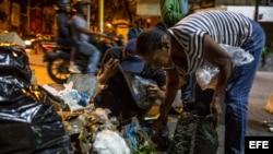 Varias personas buscan comida entre bolsas de basura en Caracas.