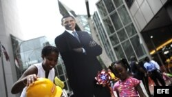 Unos niños posan junto a una imagen del presidente estadounidense, Barack Obama, en el centro de Charlotte, Carolina del Norte, (EEUU).