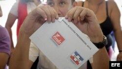 Un miembro de la Junta Receptora de Votos sostiene una papeleta