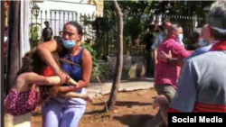 Una oficial vestida de civil, reprime a una activista frente al Ministerio de Cultura.