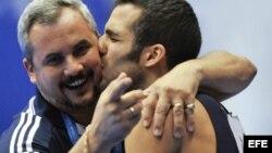 Danell Leyva besa a su entrenador y padrastro Yin Álvarez tras ganar el oro en la prueba de paralelas del campeonato Mundial de Gimnasia Artística el 16 de octubre de 2011, en Tokio, Japón.