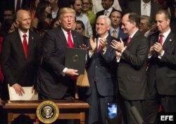 El presidente estadounidense, Donald J. Trump, muestra el memorando presidencial sobre la política con Cuba al finalizar su discurso en el teatro Manuel Artime de la Pequeña Habana.