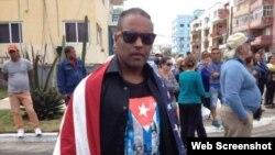 Daniel Llorente se manifiesta envuelto en una bandera estadounidense a la llegada del crucero Adonia a La Habana, en mayo de 2016.