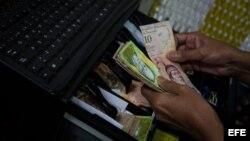 Un hombre guarda dinero en una máquina registradora en Caracas (Venezuela).