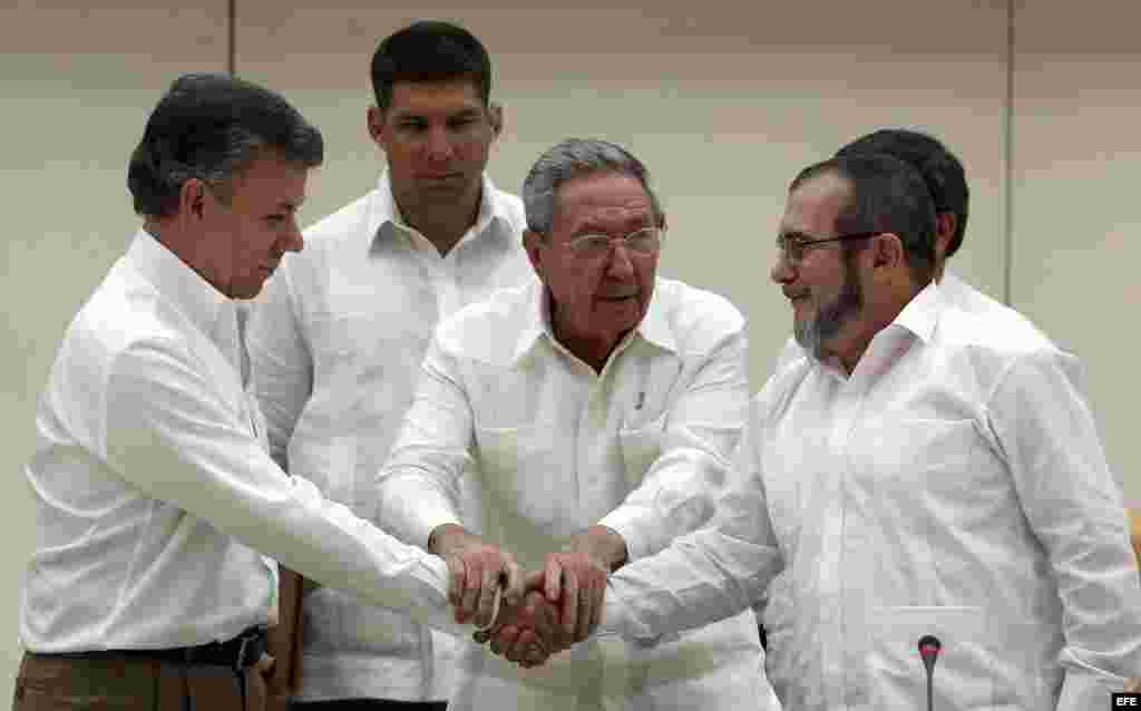 """Raul Castro abraza a Juan Manuel Santos y al líder de las FARC, Rodrigo Londoño, alias """"Timochenko"""", tras la firma del acuerdo."""