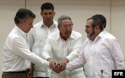 """Raúl Castro abraza a Juan Manuel Santos y al líder de las FARC, Rodrigo Londoño, alias """"Timochenko"""", tras la firma del acuerdo."""