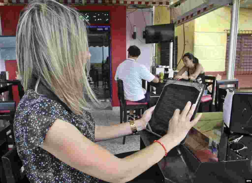 Una joven observa el menú en una tableta en un restaurante de La Habana.