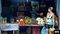 Un hombre le vende productos del campo a una mujer en Santiago de Cuba.