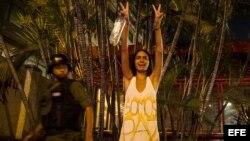 Una mujer hace un llamado a la paz mientras protestantes se enfrentan con miembros de la Guardia Nacional Bolivariana (GNB.