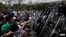Manifestantes se enfrentan con integrantes de la Policía Nacional Bolivariana durante una protesta en la Universidad Central de Venezuela.