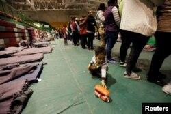 Un niño juega con un juguete mientras los migrantes de América Central hacen cola para comer en un refugio improvisado en Ciudad Juárez, México.