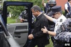 El expresidente salvadoreño Francisco Flores (i) es trasladado a una celda policial.