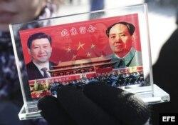 Un vendedor expone un recuerdo con la imagen del presidente chino, Xi Jinping (izq), y del fallecido líder Mao Zedong (dcha) en la Plaza de Tiananmen, en Pekín (China).