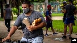 Un hombre carga el pan mientras viaja en bicicleta por una calle de La Habana. (AP/Ramon Espinosa)