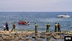 Guardafronteras observan a un grupo de cubanos a bordo de una embarcación rústica que intenta salir por mar hacia Estados Unidos.