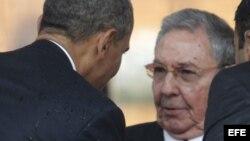 El presidente estadounidense, Barack Obama (i), saluda a Raúl Castro, durante el servicio religioso oficial del expresidente sudafricano Nelson Mandela en el estadio FNB de Soweto en Johannesburgo.
