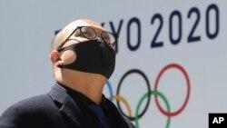 Un hombre se protege del coronavirus frente a un logo de los Juegos de Tokio. AP Photo/Koji Sasahara
