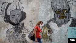 Una mujer usa una máscara protectora contra el coronavirus en una calle de La Habana. (YAMIL LAGE / AFP)