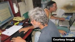 Febles, atrás, y su colega Luis Cino trabajan en la redacción de Primavera Digital.