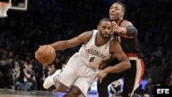 El jugador Deron Williams (C) de los Brooklyn Nets disputa el balón con Damian Lillard (d) de los Portland Trail Blazers durante el primer cuarto de su partido de la NBA en el Barclays Center en Brooklyn (Estados Unidos).