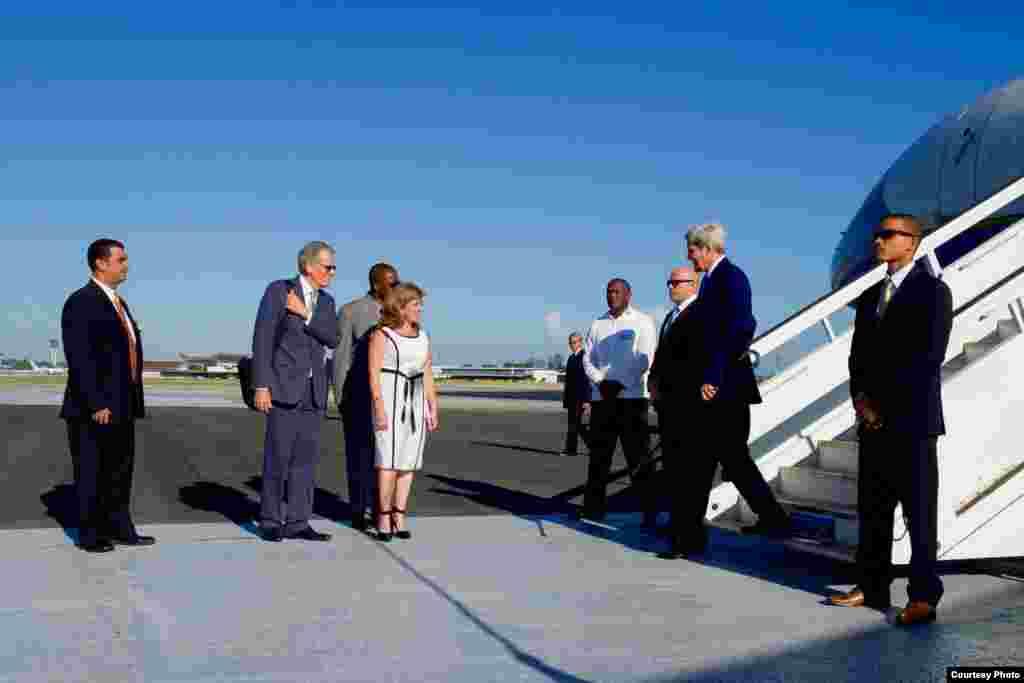 John Kerry es recibido en La Habana por la subdirectora de protocolo del Ministerio de Relaciones Exteriores de Cuba, Lydia González Navarro, y por Jeffrey DeLaurentis, encargado de negocios de la embajada estadounidense.