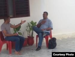 Pastor Alain Toledano mientras era notificado del posible desalojo por Robert Noa Frómeta, encargado de la Oficina de Asuntos Religiosos del Partido Comunista de Cuba (PCC) en Santiago de Cuba (i-d).
