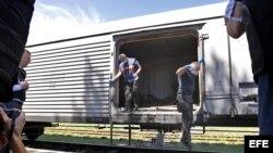 Expertos forenses holandeses saltan de un vagón refrigerado tras revisar alguno de los cadáveres de las víctimas del vuelo MH17.