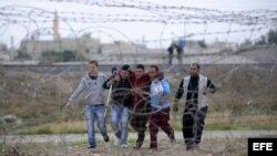 Varios sirios ayudan a un herido (3º izq) mientras huyen de su país en la región de Rasulayn