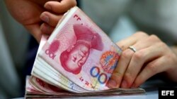 Empleado de banca cuenta billetes en la localidad de Suining, en la provincia china de Sichuan, China.