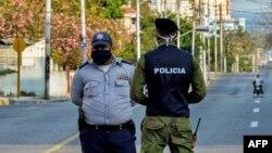Oficiales de policía vigilan la entrada a un barrio del Vedado, en La Habana, cerrado por el coronavirus.