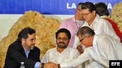 El representante de Cuba, Rodolfo Benítez (i), saluda al integrante de las Fuerzas Armadas Revolucionarias de Colombia (FARC) Rodrigo Granda (d), alias Ricardo Téllez, junto al segundo jefe de las FARC, Luciano Marín. Archivo.