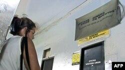 Una mujer espera afuera de Western Unión en La Habana
